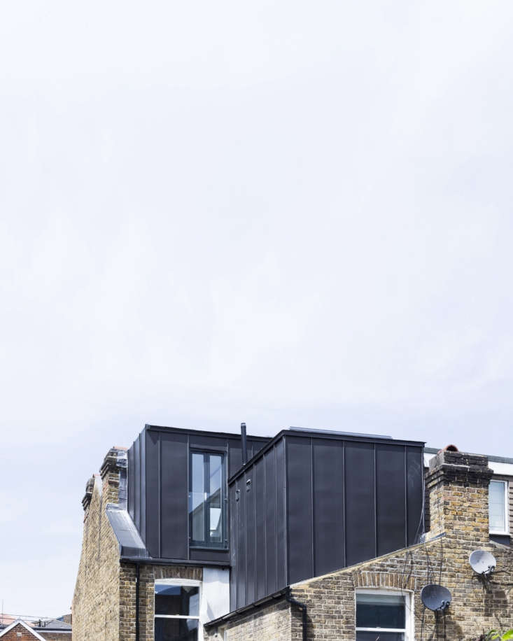 Under the Eaves A Brick House Reinvention in South London by Simon Astridge On the roof, two standing seam metal additions extend the master bedroom and bath. The color was selected to work with the dark gray of the neighboring rooflines.