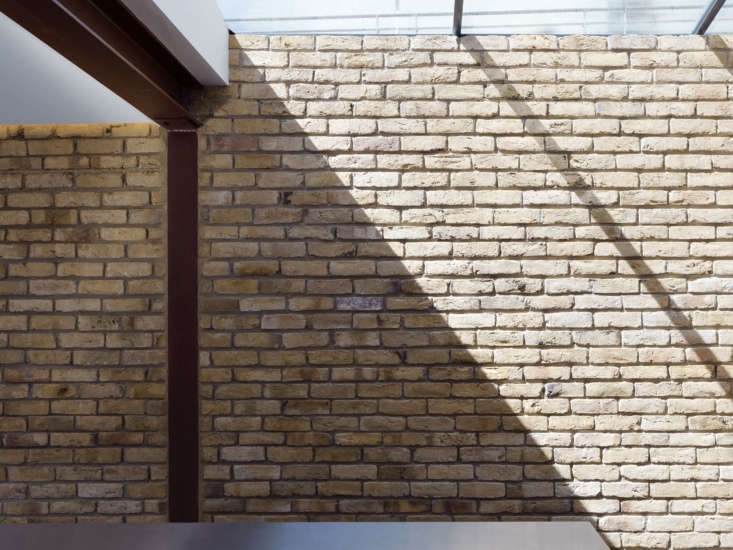 In the kitchen, a wall of reclaimed London stock brick matches the brick on the exterior. The new structure has exposed steel supports and I-beams that are spray-painted burgundy. Also note the &#8
