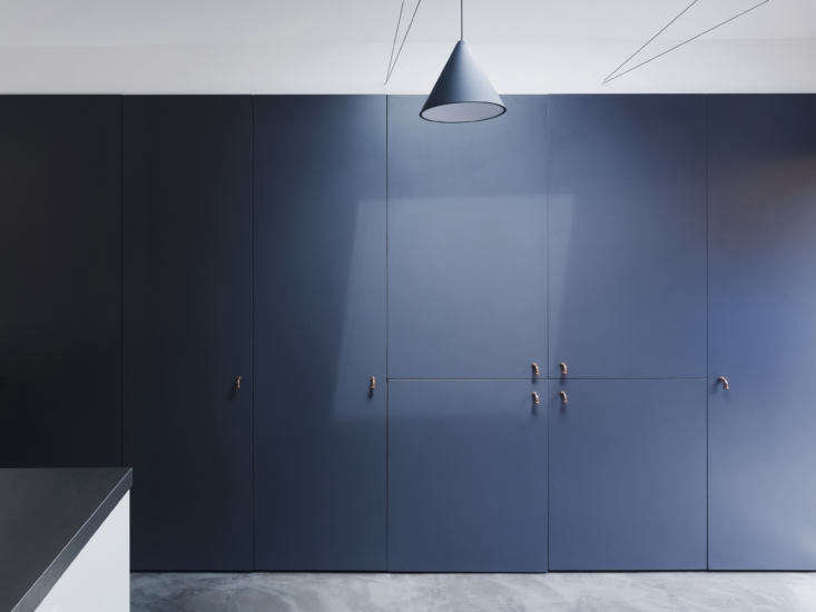 The refrigerator is concealed on the storage wall, which has door pulls made from bent copper plumbing pipes.
