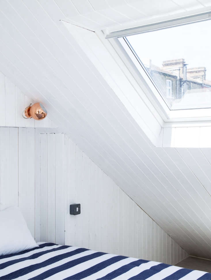 The skylight in the roof is also paneled. The copper sconce was chosen for contrast. For something similar, consider the Benny Frandsen Ball Copper Wall Lamp.