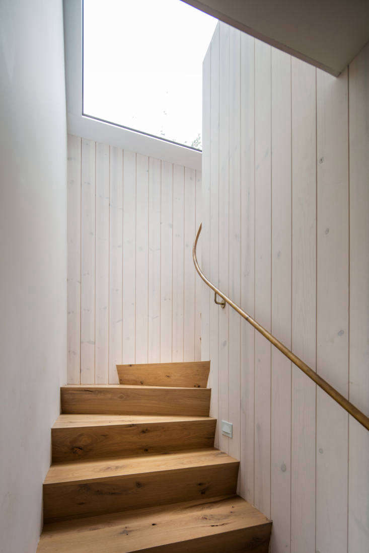 The walls on both levels are clad in whitewashed heart pine. The stair rail is made of unlacquered brass.