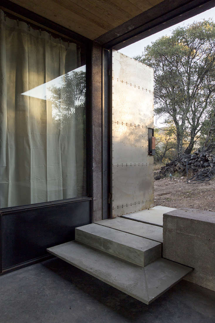 The doors have leather handles custom designed and made by Dust. The doorway facing the hillside has concrete steps leading into the main hall.