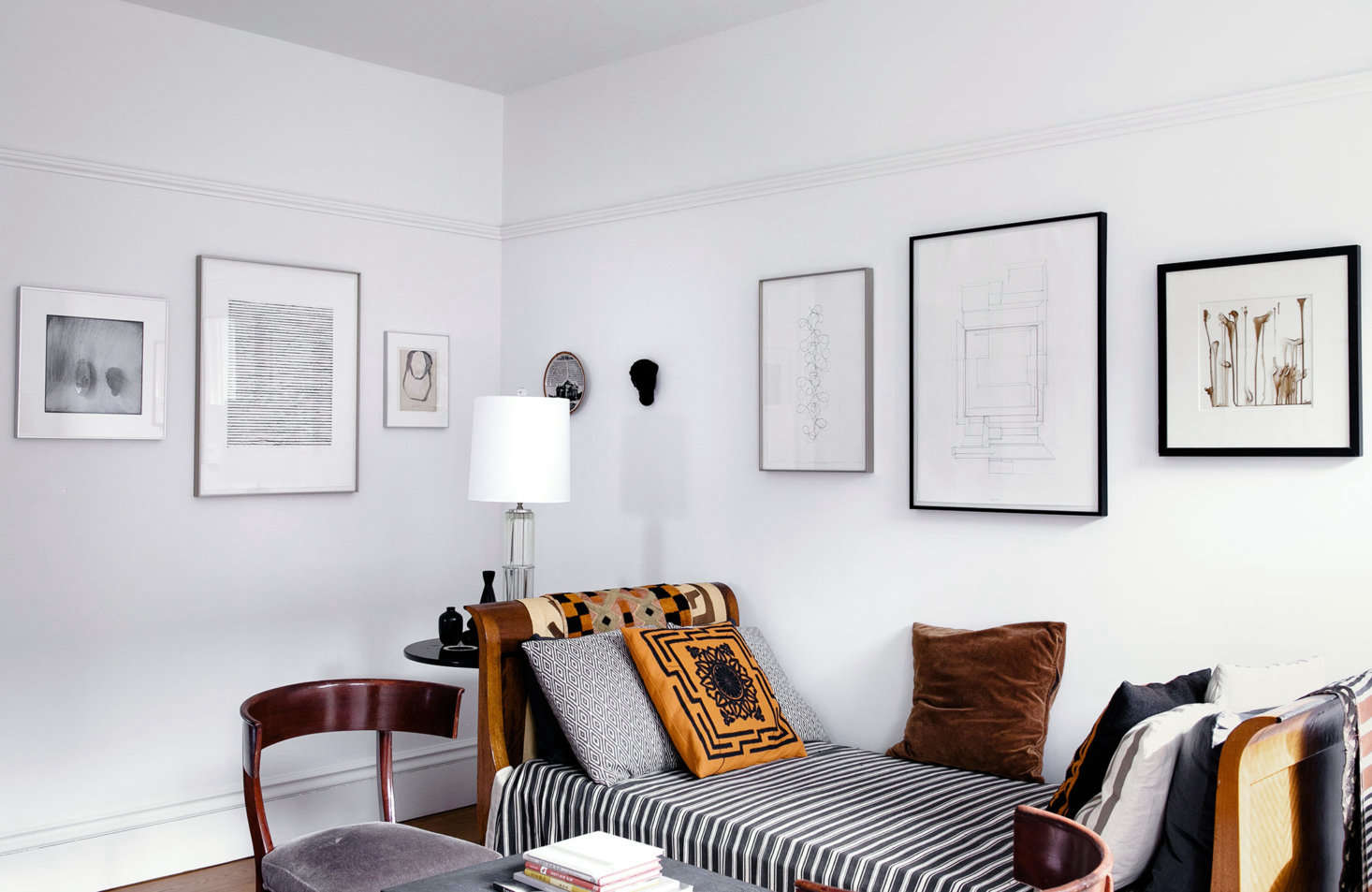 The sitting room enjoys views into both the living and dining rooms. To emphasize the seamless flow between spaces, the design duo hung a continuous line of art leading from room to room.