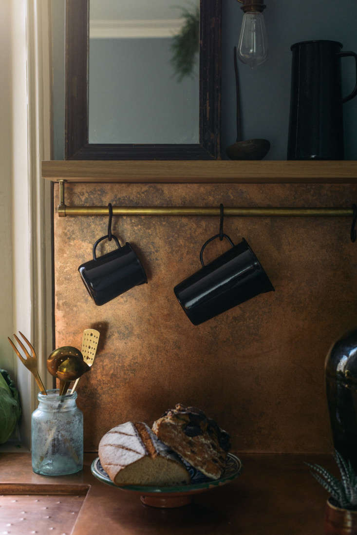 As a final decorative touch, Parker displays a range of black and dark green enamelware from Falcon; here, it hangs from an unpolished brass storage rail.
