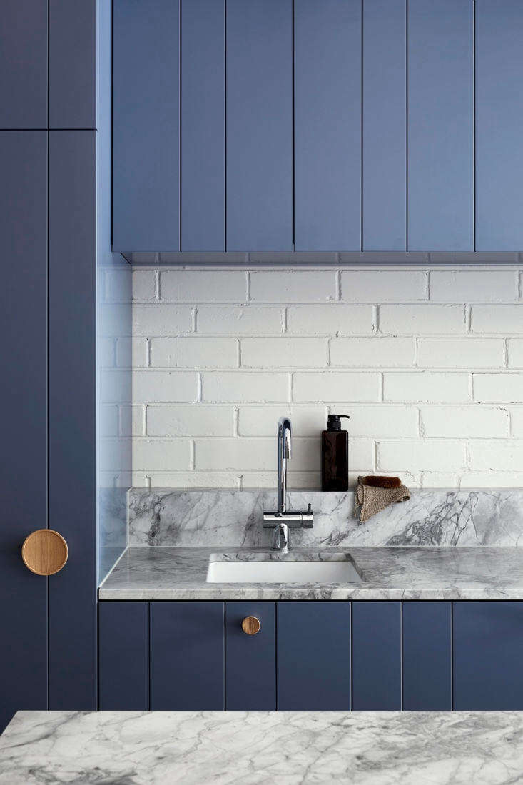 The countertops are Super White Quartzite. The backsplash is a structural brick wall, painted white. TheSoap Dispenser is from Muji.