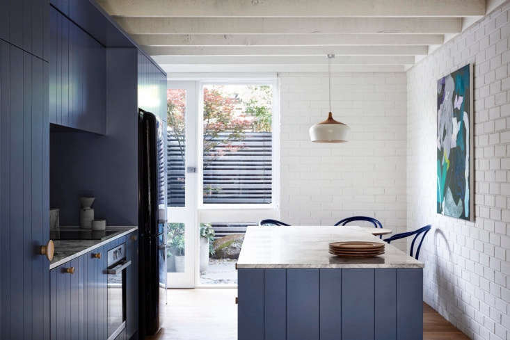 The cabinets are painted in blue-gray Buoyant from paint purveyor Dulux. The architect retained the exposed beam ceiling to extend the retro timber theme.