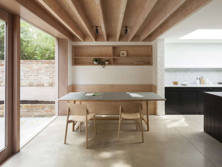 A Kismet Renovation in Highbury London by OSullivan Skoufoglou Architects The dining area has a white slurried brick wall, a built in banquette, and a recessed shelf in Douglas fir, with exposed joists above.
