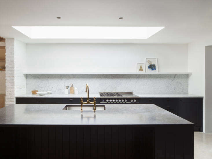 A Kismet Renovation in Highbury London by OSullivan Skoufoglou Architects A new skylight over the kitchen helps to naturally illuminate the space, which is painted in Farrow & Ball Wimborne White—just one shade away from pure white. The custom cabinets by Handmade Kitchens are finished in blue black Railings paint, also by Farrow & Ball. The Carrara marble counter and backsplash are from Rossi Stoneworks and the island top is Belgian bluestone. The range is the Ilve Roma Twin Range Cooker; it's the only visible appliance in the kitchen; others are panel ready Bosch appliances. The island faucet is Perrin & Rowe&#8\2\17;s Ionian Deck Mount Taps in a gold finish.