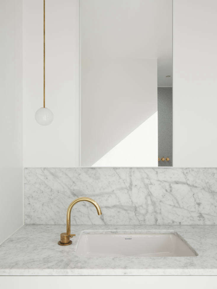 A Kismet Renovation in Highbury London by OSullivan Skoufoglou Architects The faucet is a Vola One Handle Mixer 590V in natural brass and the sink is the Duravit D Code Vanity Basin. The light is Michael Anastassiades's Brass Pendant 80 Rod.