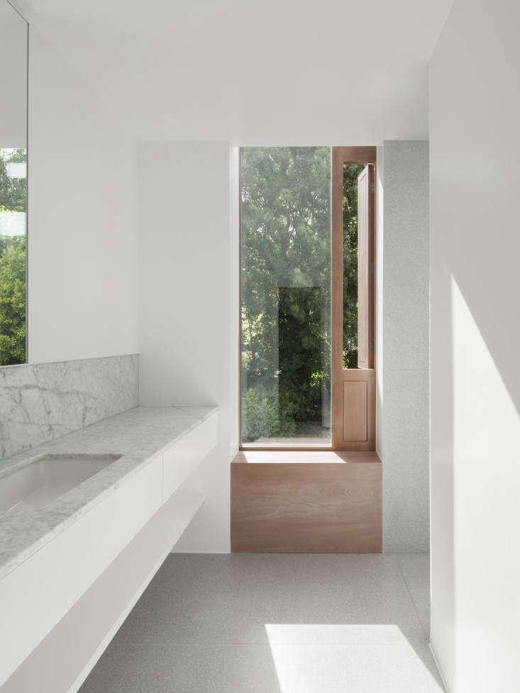 A Kismet Renovation in Highbury London by OSullivan Skoufoglou Architects The first floor bathroom was refurbished as part of the project. The architects installed a glass panel window with a sapele wood frame and single shutter for ventilation. Countertops, as in the kitchen, are Carrara marble from Rossi Stoneworks and the floors are Terrazzo Cement by In Opera Group.