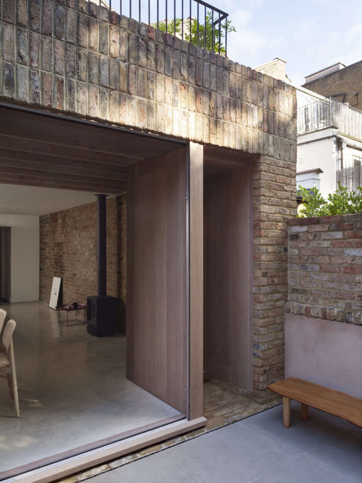 A Kismet Renovation in Highbury London by OSullivan Skoufoglou Architects A detail of the extension, which opens onto a sunken brick and concrete paver patio. The live edge bench is made from a single oak plank from Andrea and Pete's previous garden in Suffolk that was customized with oak legs byAndrew Tutka.