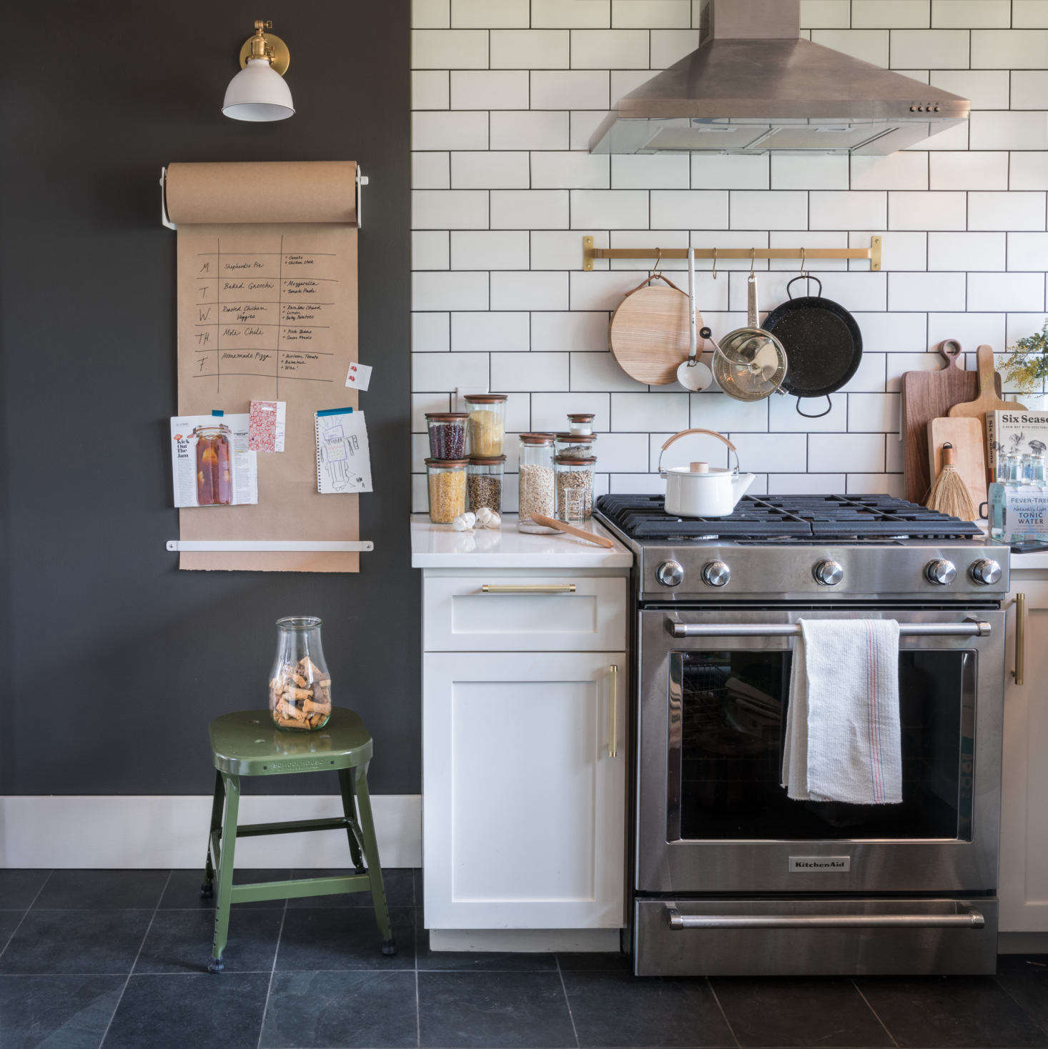 A subway tile kitchen with a Wall-Mounted Paper Holder and brass Utility Rail from Schoolhouse.