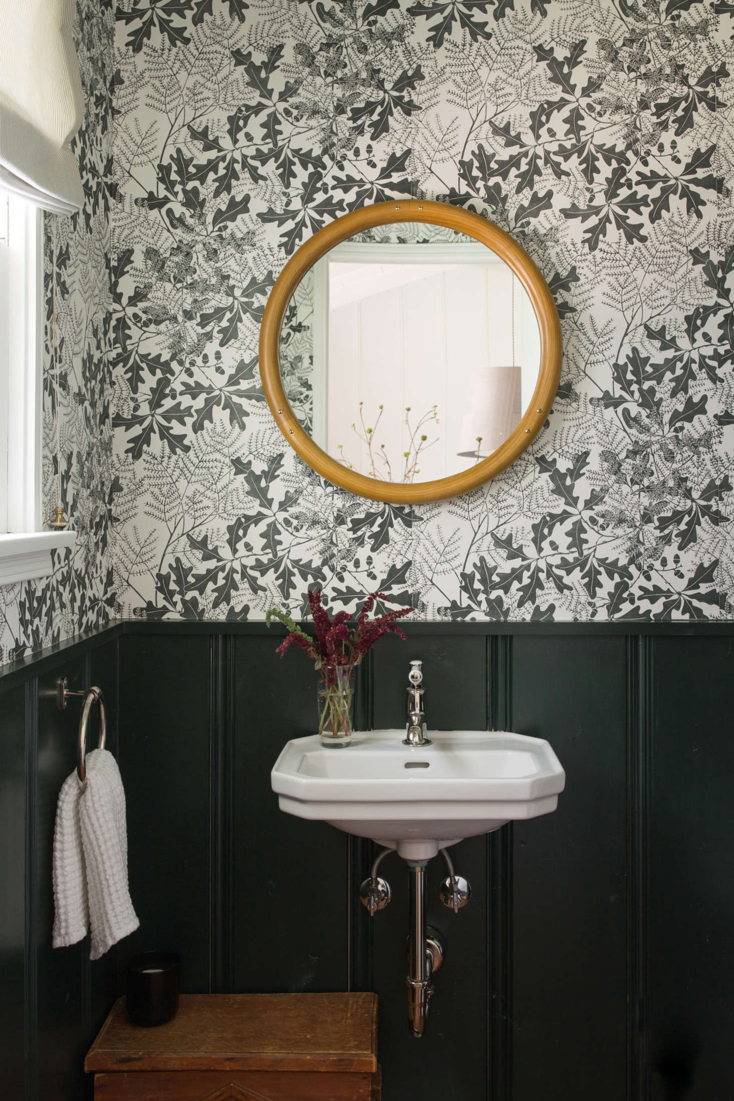 The relocated powder room, with Oakleaf wallpaper by Marthe Armitage from Hamilton Weston. The couple had it custom-printed in an olive green to match the wainscoting, which is painted in Portola&#8