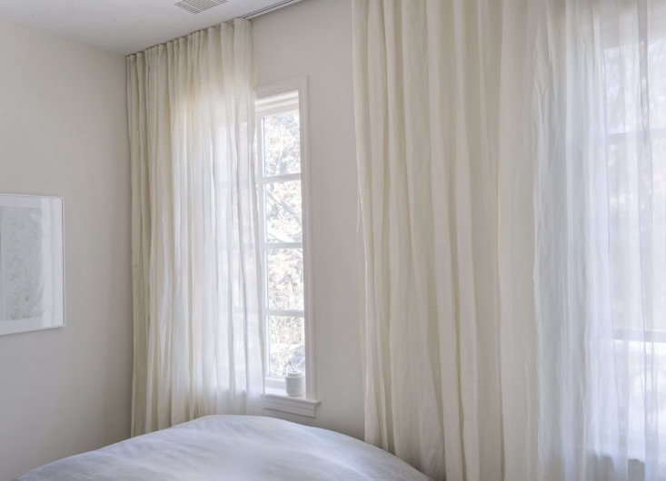 """Kinnasand curtains are hung on a track in both upstairs bedrooms to create an open atmosphere while """"at the same time, functioning as a private and discreet retreat."""" In the main bedroom, seen here, the curtains run the length of the wall to cover both windows rather than hanging on individual curtain rods."""