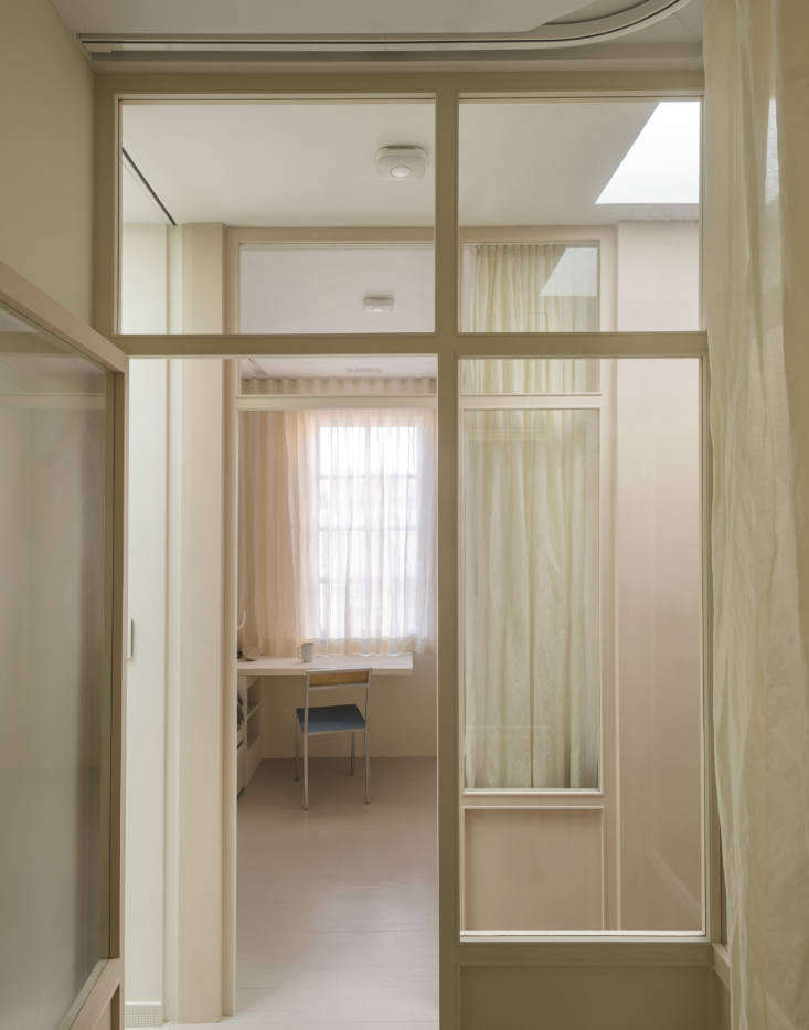 """With an idea borrowed from Parisian interiors and Shaker houses, Studio Oink solved the problem of a lightless hallway by tearing down the existing walls between the bedrooms and creating a glass wall. """"You can guide the light into smaller or hidden rooms without losing a private atmosphere,"""" says Lea."""