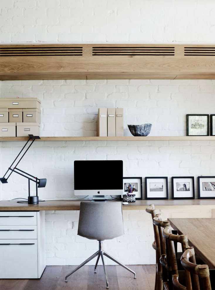 A simple, built-in oak plank serves as a work surface, and a custom file cabinet matches the kitchen cabinets. Throughout the house, the designers installed walls of recycled brick, finished with matte white paint.