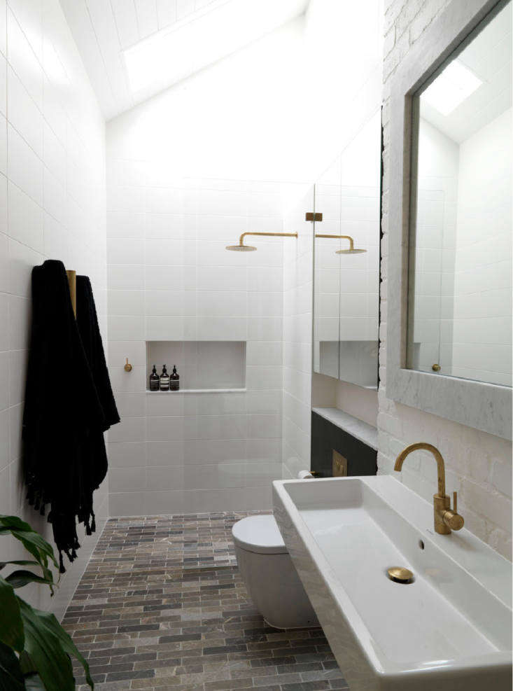 The master bath has a tumbled marble floor, brass fixtures, and a skylight for natural light.