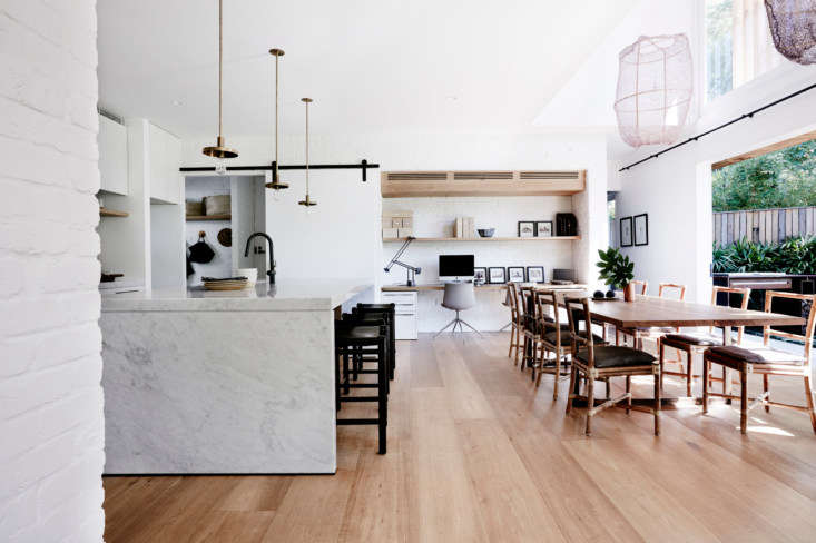 The main room is a combined kitchen and dining with a desk space along the far wall. The room opens onto the backyard via full-height sliding glass doors, and is open to the living room, in the foreground.
