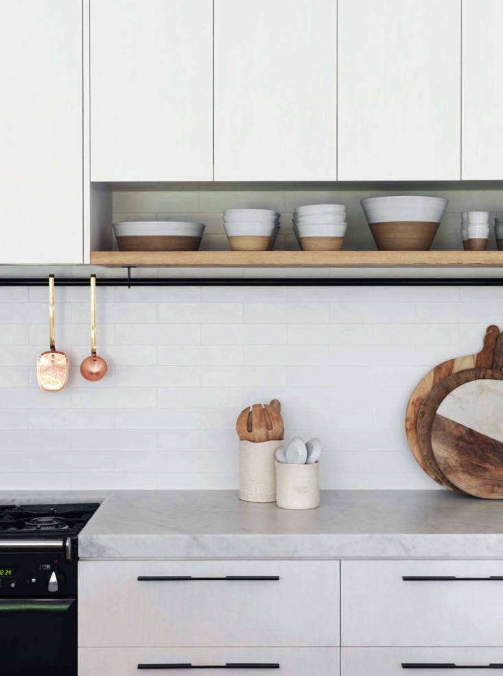 The countertops are honed Carrara marble. A black steel rail for hanging kitchen tools spans the width of the back kitchen wall.