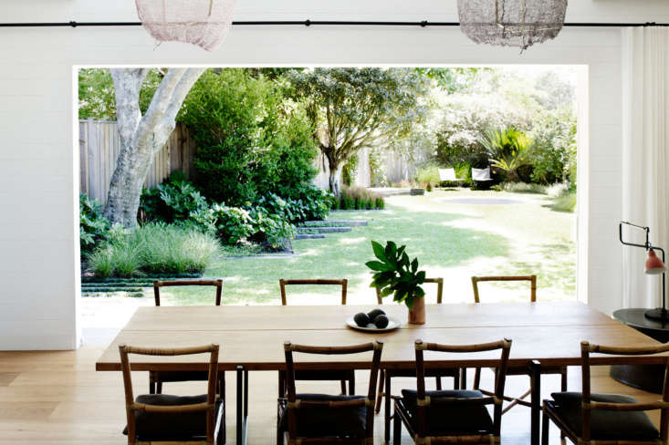Both the dining and living rooms open completely onto the backyard. (See the full landscape inDownsizing a House to Expand the Garden: At Home with Landscape Architect William Dangar.) The dining table was made by Specified Storeandthe chairs are byGervasoni—they&#8