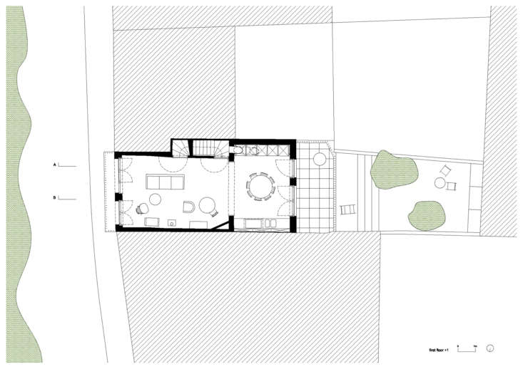 The next floor up, showing the living area and kitchen, with the staircase and cabinetry set into the walls. This floor also opens onto the balcony (on the street side) and a sunny terrace (in back). There is a top floor, which the architects say is fitted with &#8
