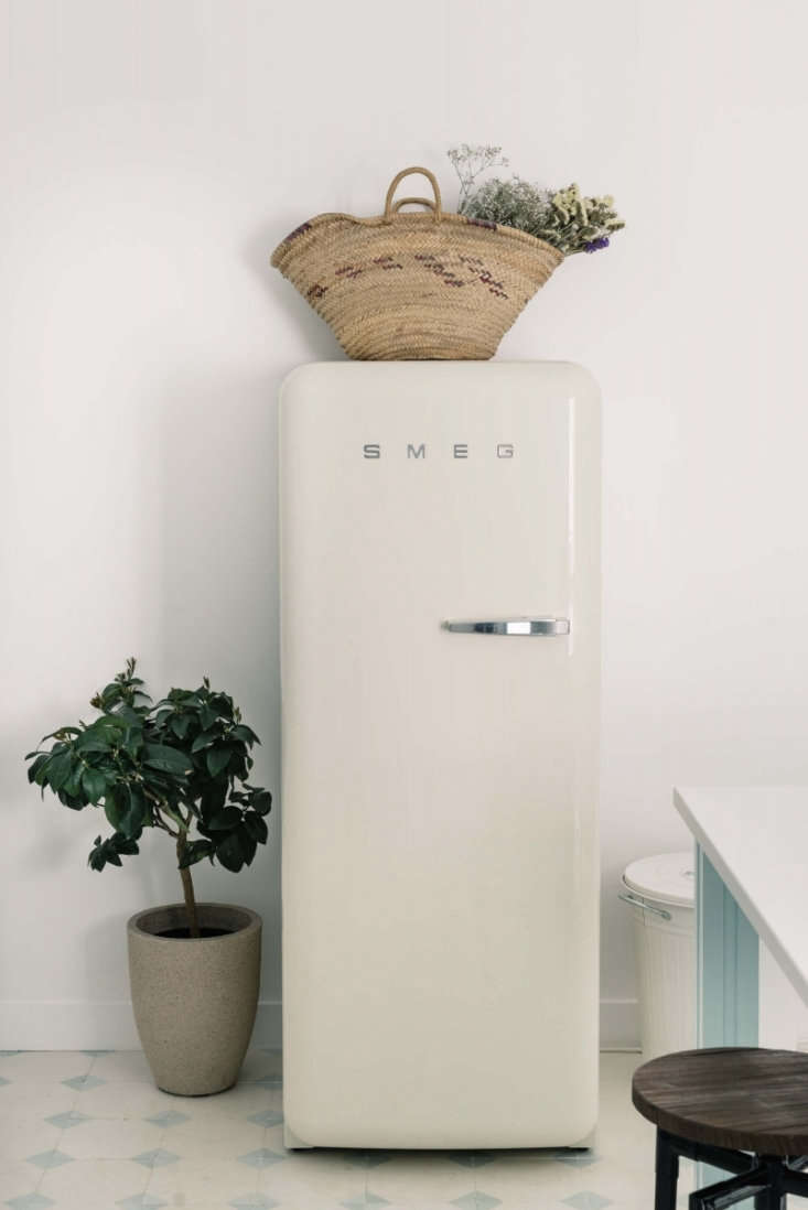A white Smeg refrigerator sits opposite the kitchen island, next to the door.