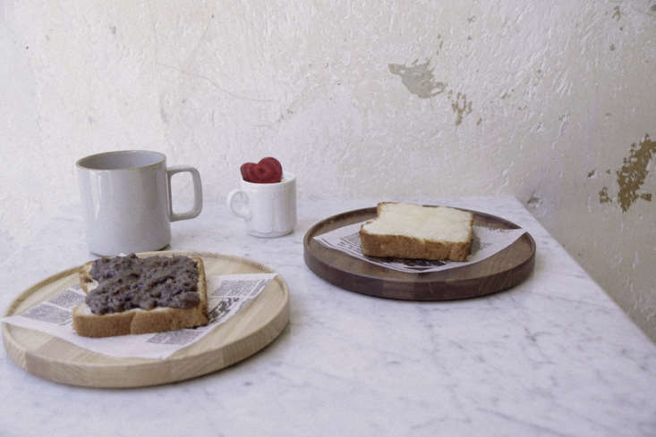 Among the table settings: simple ceramics and newsprint.