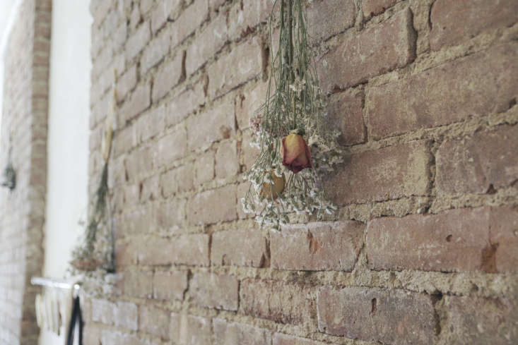 Along the exposed brick wall: imperfect and ad-hoc bundles of dried flowers.