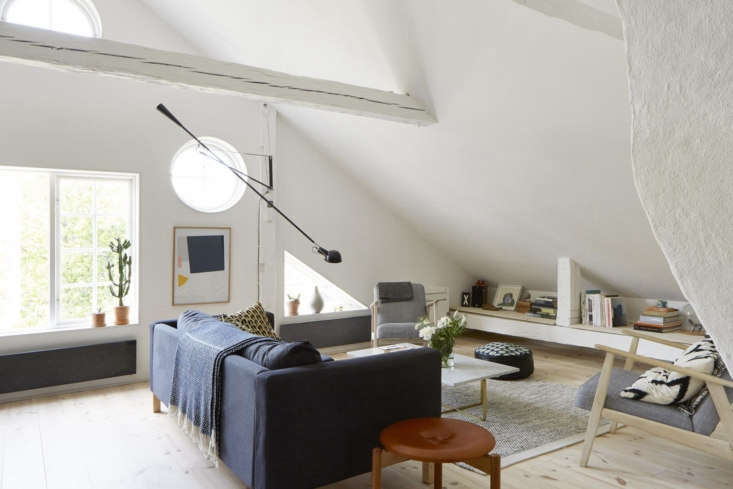 The main room gets ample light from six windows on one side, two of which are triangular and three circular.