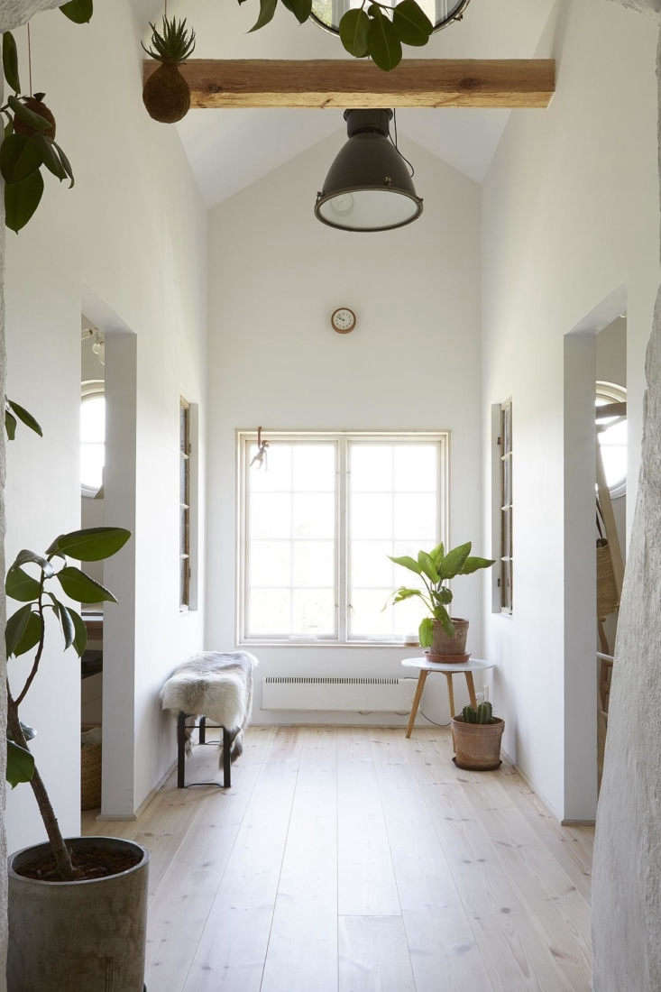 The windows at the end of the hall open onto the lake. Floors throughout the apartment are reclaimed wood from Dala Floda, Sweden, stained white.