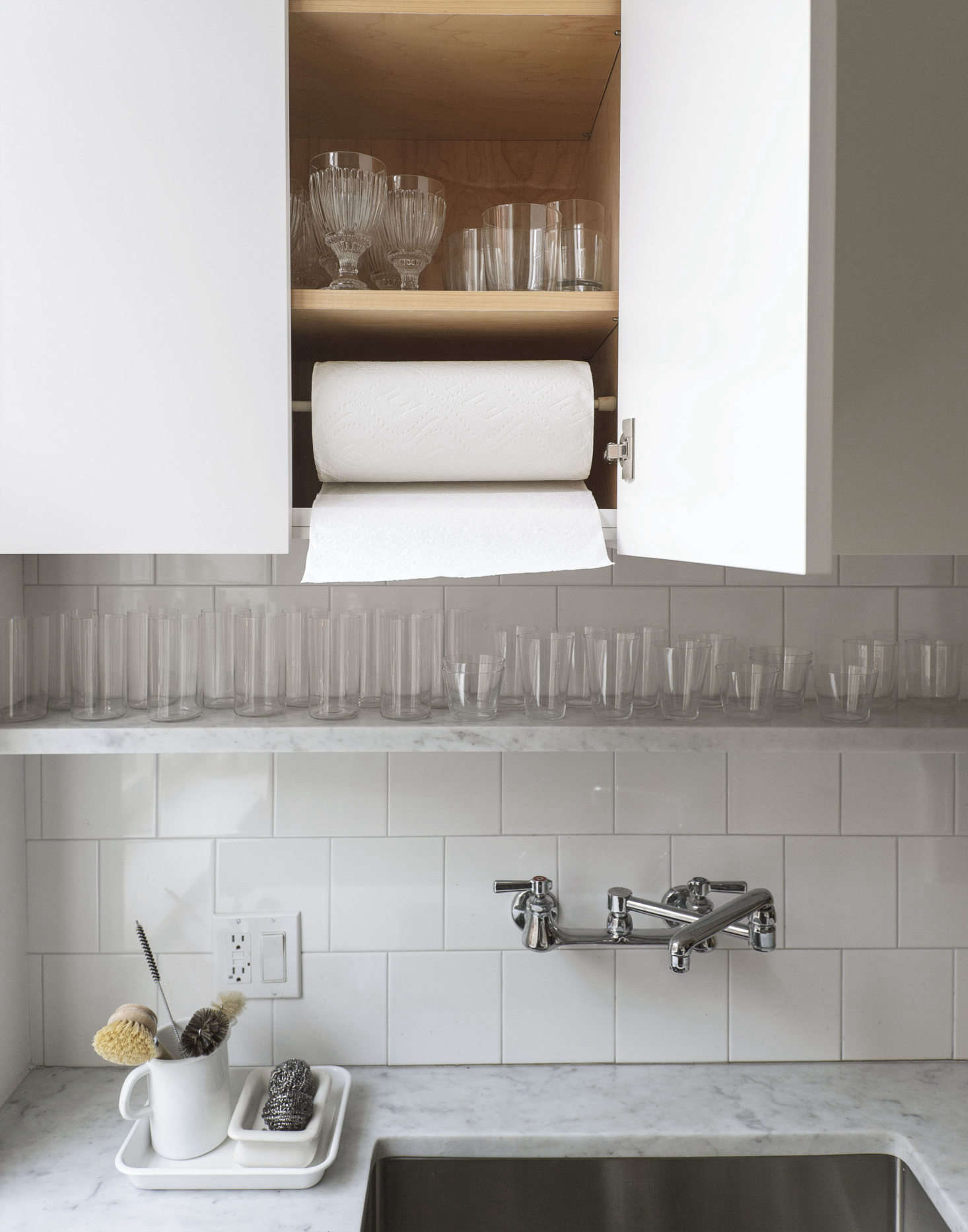 The wall-mounted Chicago Kitchen Faucet with articulated spout is a model we've used before; it's well priced, American made, and incredibly durable. We installed a dowel in the cabinet above the sink to hold paper towels. (See Aha! Hack: Tension Rod as Paper Towel Holder.)