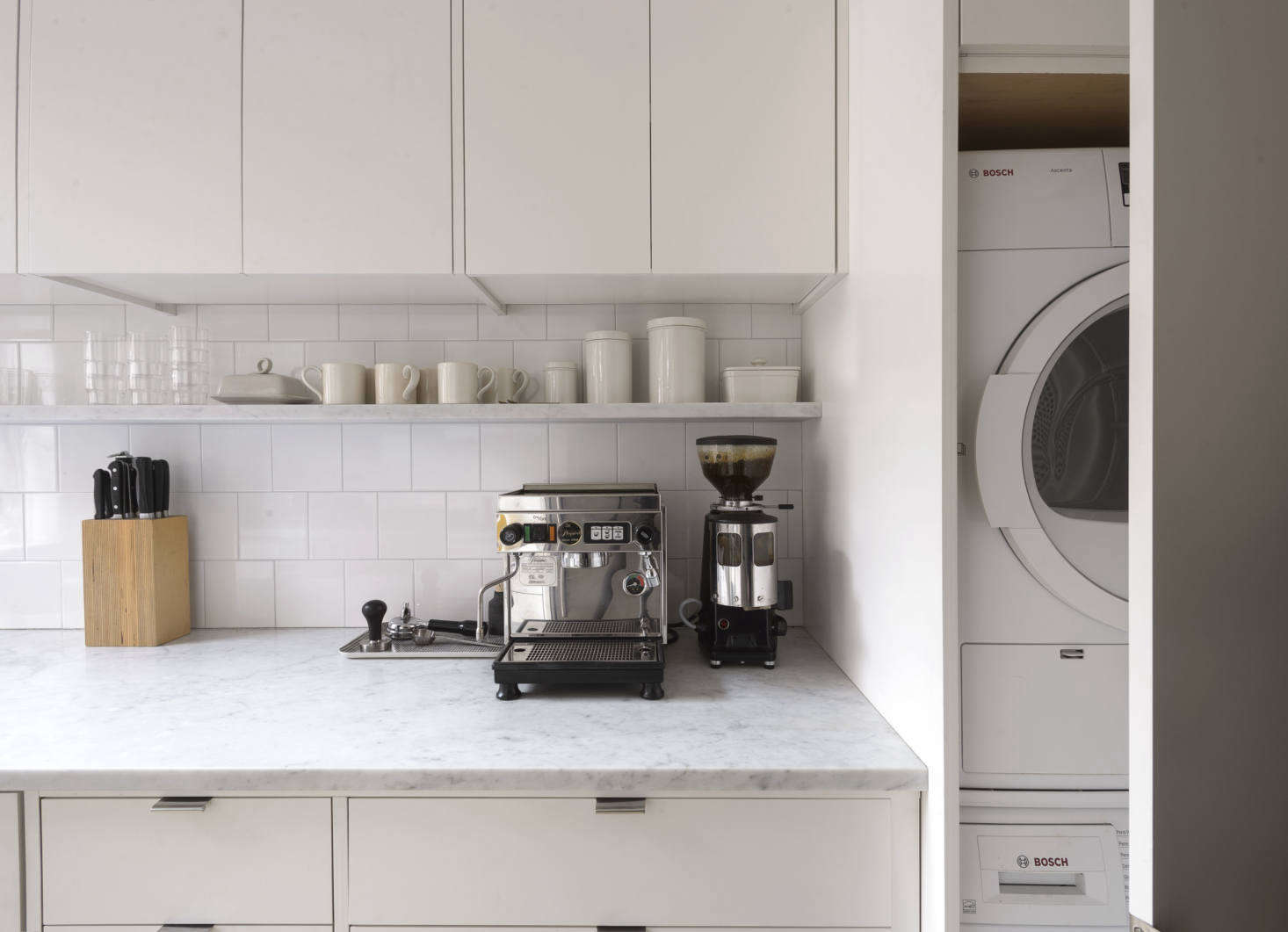 We tucked a stacked Bosch washer/dryer behind a full-height door; instant laundry room.