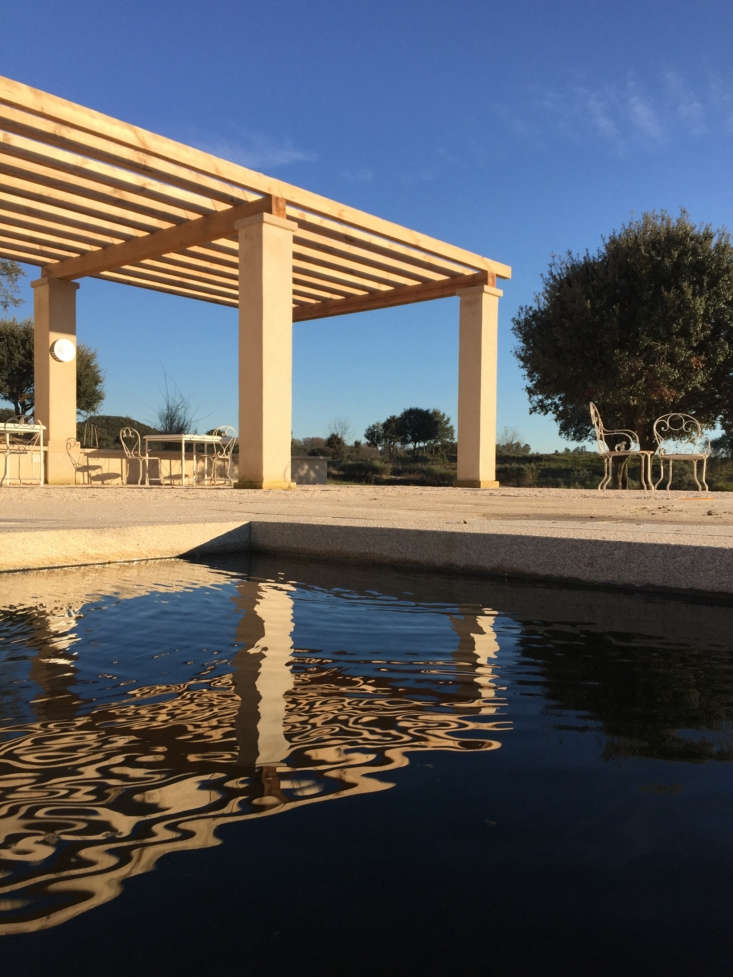 a pergola for shady outdoor living rises next to the granite framed swimming po 24