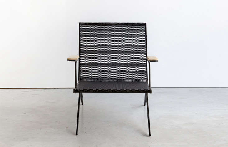 Profile is a black-painted, steel-framed chair with a perforated seat and wood armrest. It&#8