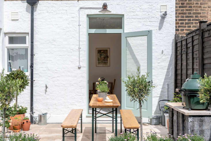 "The outdoor space features a German Biergarten Table and hand-built BBQ with a Big Green Egg. The back facade is painted Dulux Pure Brilliant White and the door is Farrow & Ball Green Blue. The industrial fixture above the door came from a friend: ""He and his partner moved to a very stylish Sixties development in Hatfield, and this didn't quite go with their refit. We love it, though,"" says Mina."