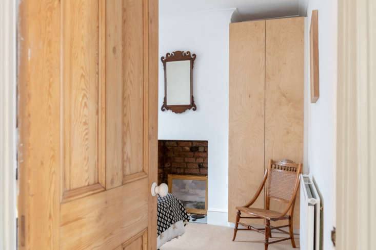 The oak doors are original to the building, with new porcelain knobs from Homebase. The bedroom beyond has a custom plywood cabinet fitted to the alcove and Mina's grandmother's nursing chair and antique mirror.