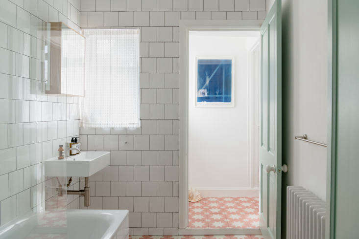 "The couple renovated the bathroom with white square tiles from B&Q in London; for the floor, they used Pink Pradena Tile from Bert & May. Says Mina: ""I adore tiles and always have and the opportunity to pick my own for my first home was almost too much pressure! I wanted something simultaneously Arabesque and modern. I think, I hope, we got there in the end."" The mirrored cabinet is the Wireworks Slimline Cabinet, the sink is a Bauhaus Turin Wall-Mounted Basin, the faucet is a Vola HVsrc="