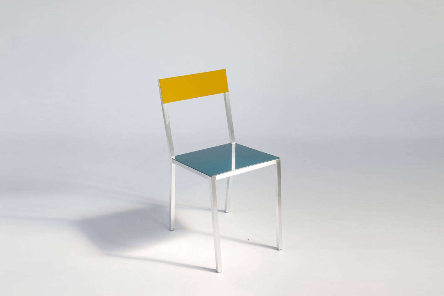 At the desk is the Muller van Severen First Chair made of lacquered steel and polyethylene; $loading=