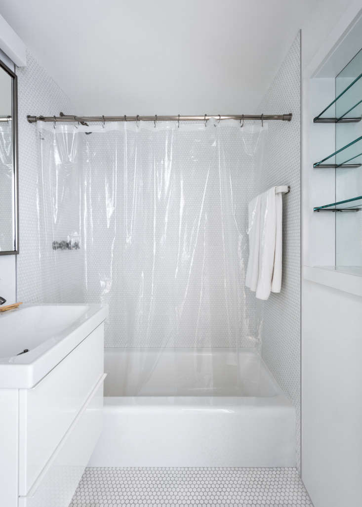 The bathroom floor and three sides of the shower are tiled in small penny tile from Daltile. (The grout is Silver Shadow grout from Laticrete.) A clear shower curtain—not for the modest—makes the room feel lighter and more open.