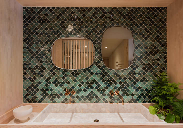 Two Vola polished brass faucets empty into a terrazzo sink with a wall ofhandmade green Moroccan tiles from Emery et Cie behind.