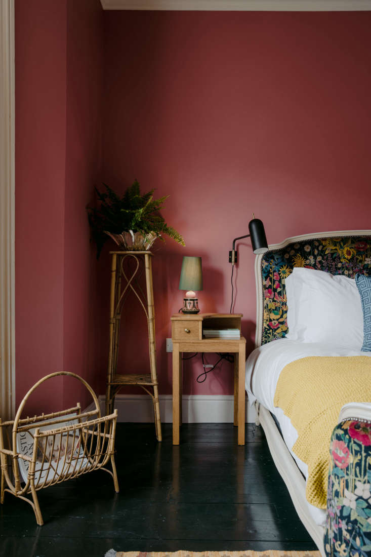 """At this inventively colorful English inn, walls painted a deep Rhubarb by Paint & Paper Library pairs with black floors and velvet fabric in a floral pattern by Liberty London. """"I really pushed for this color,"""" the stylist told us. """"Everyone was against it, but I got quite obsessed.&#8"""