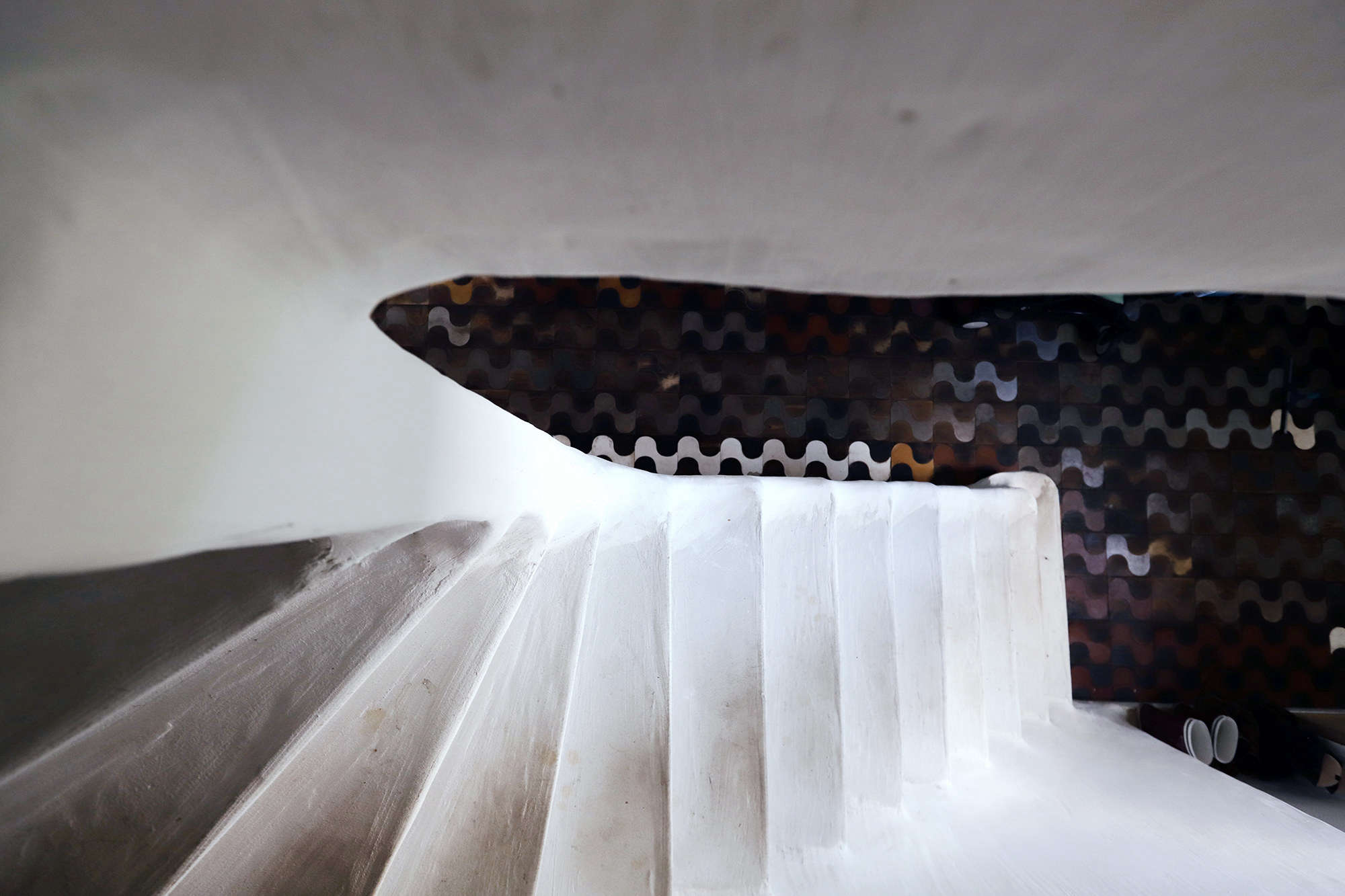 The main staircase between lower and upper floors is made of cement formed around the original stair. The floor tiles are leather, ceramic, steel, and wood, made by Valentin's sister, Miriam Loellmann, who lives and works in Rio de Janeiro, Brazil.