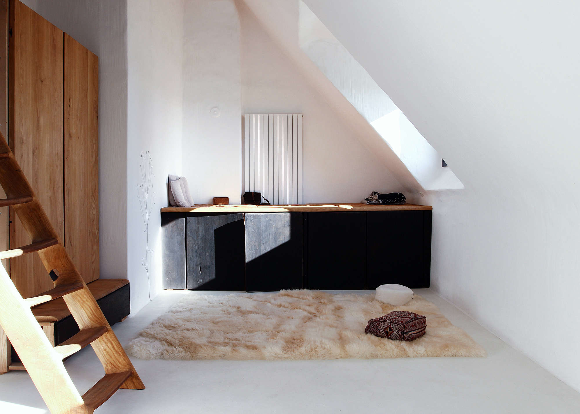 A dressing room that Valentin and his girlfriend converted for their one-year-old daughter. The built-in cabinet is made of charred oak with a leather pad on top and the staircase to the left leads to the main bedroom.
