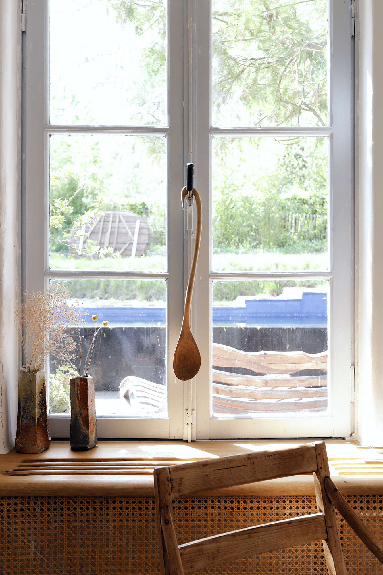 The carved wooden spoon and ceramic vases are both handmade.