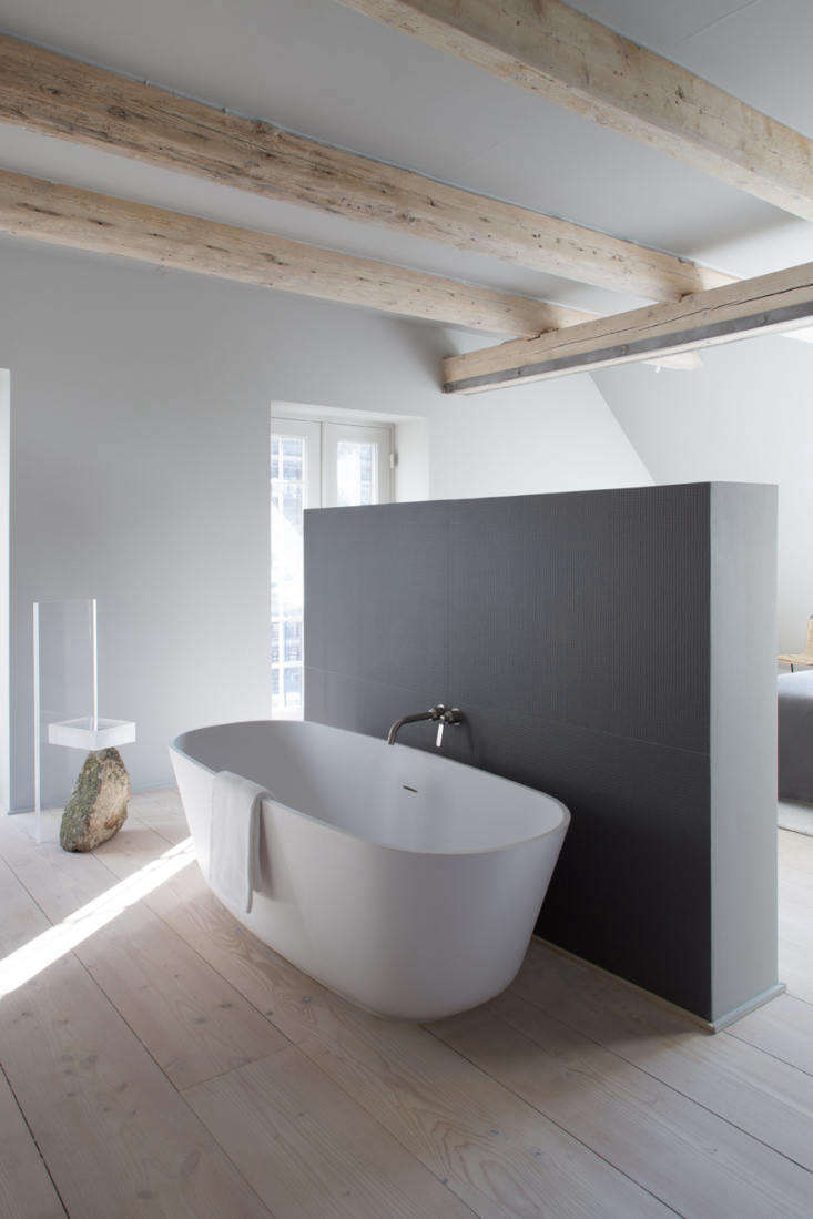 a free standing oval tub is tucked in the bathroom behind a privacy wall. 18