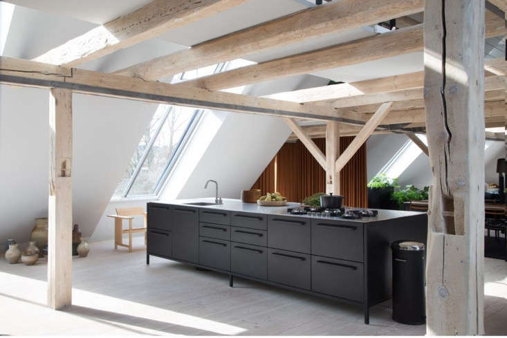 a free standing vipp kitchen stands in the centered of the open floor. the oa 12