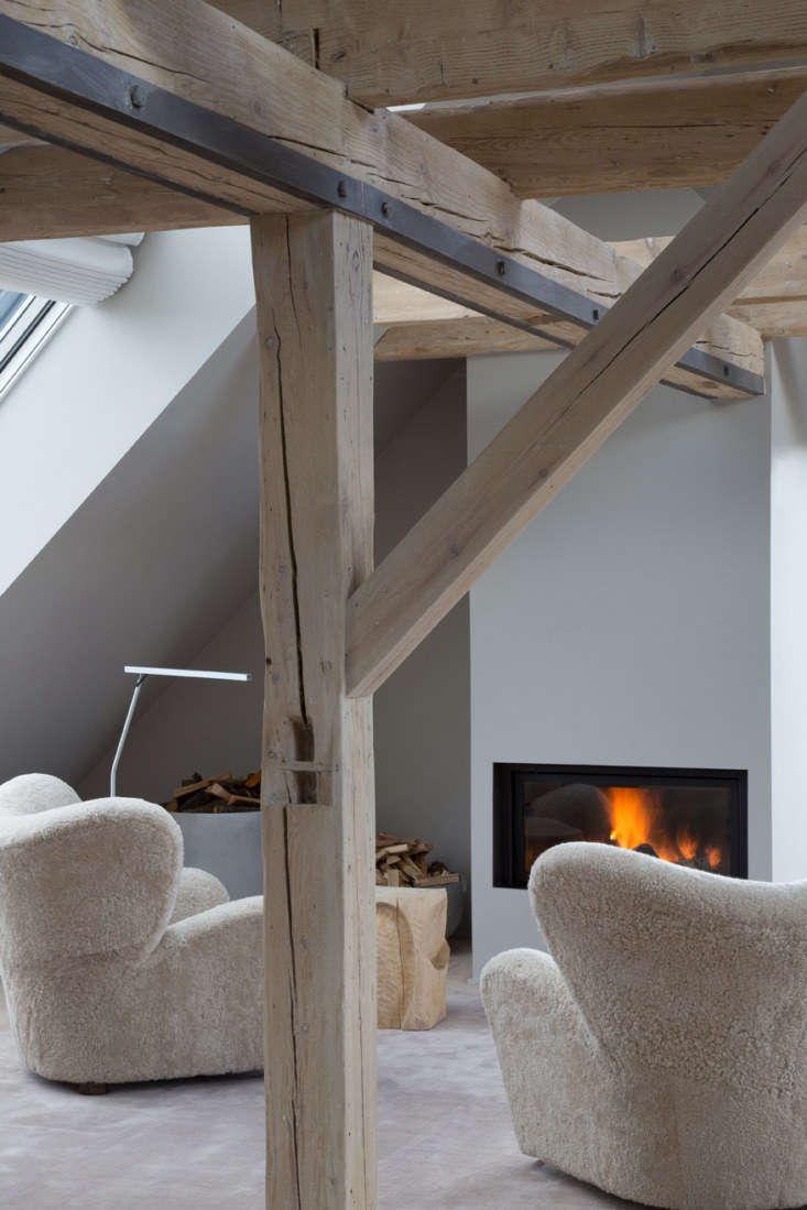 two upholstered sheepskin chairs are placed in front of the fireplace. 20