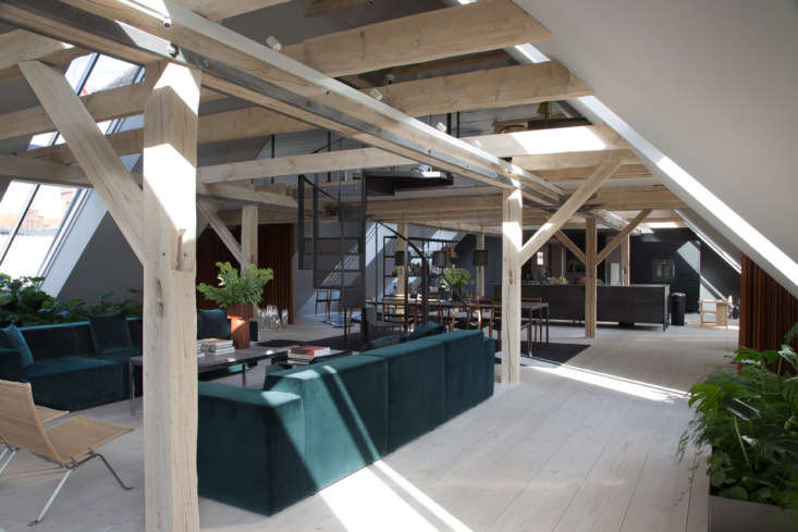 the large living space features a green velvet sofa andpoul kjaerholm pk\2\2  14