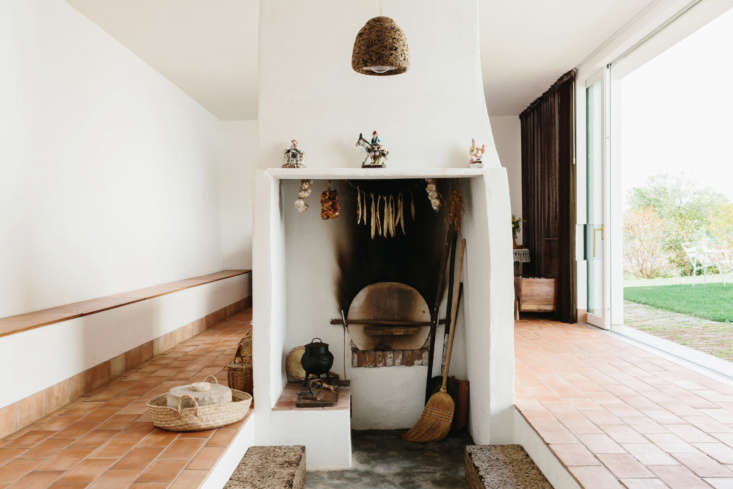 the kitchen has a traditional woodstove. the dark cork pendant light is by the  14