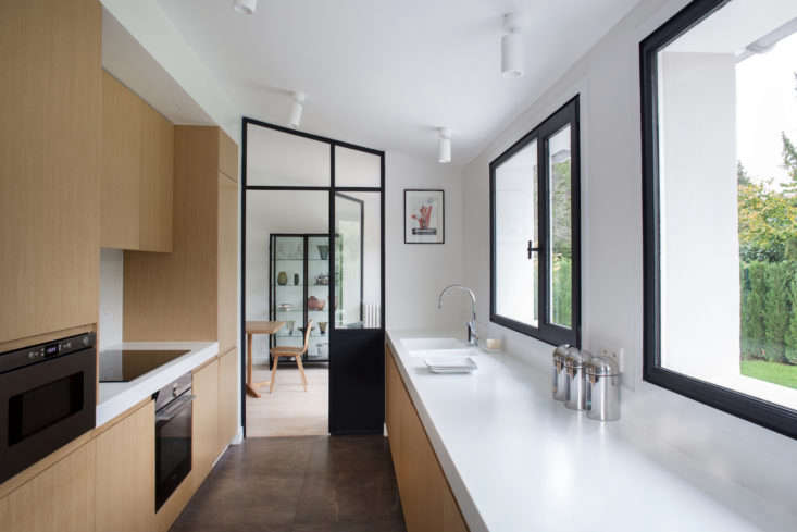 The integrated sink—with a Dornbracht faucet—is set at the end of the counter, opposite the fridge and freezer and next to a steel-framed glass door to the dining room.